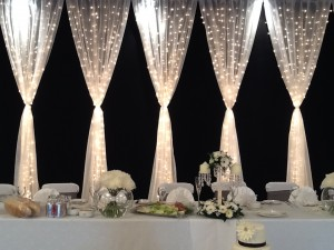 gathered fairy light curtain head table backdrop